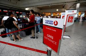 FILE PHOTO: Passengers wait in line at a Turkish Airlines counter at the international departure terminal of the Ataturk airport in Istanbul